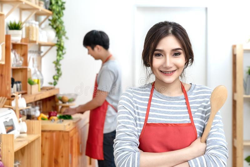 Attractive young asian couple wearing casual orange apron cooking meal in wooden kitchen at home or apartment. Young millennials royalty free stock photo