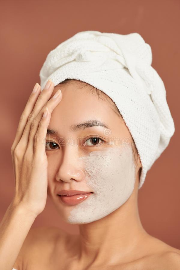 An attractive young Asian girl with a white towel on her head applied a useful clay mask stock photo