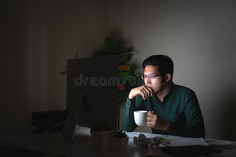 Attractive young asian man drinking coffee sitting on desk table looking at laptop computer in dark late night working feeling royalty free stock images