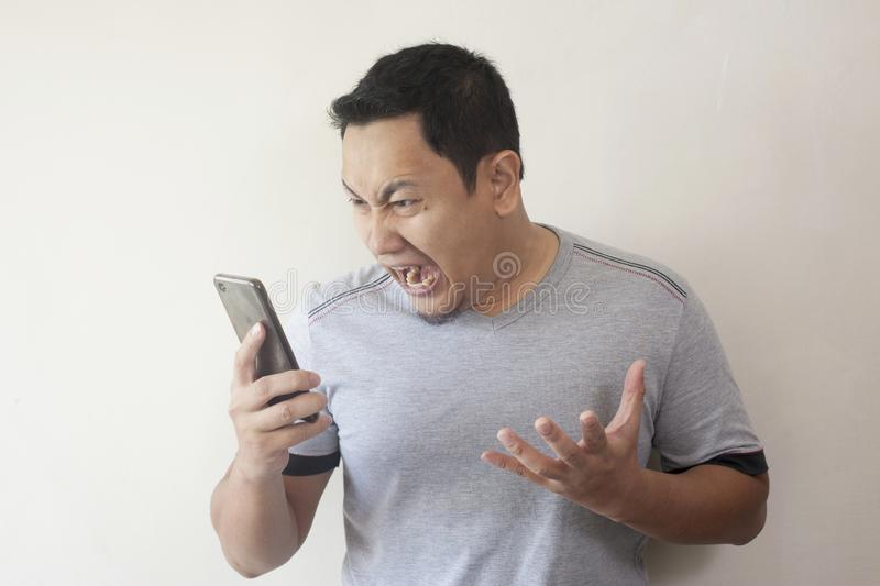 Young Man Getting Bad News on Phone, Shocked and Angry stock photos