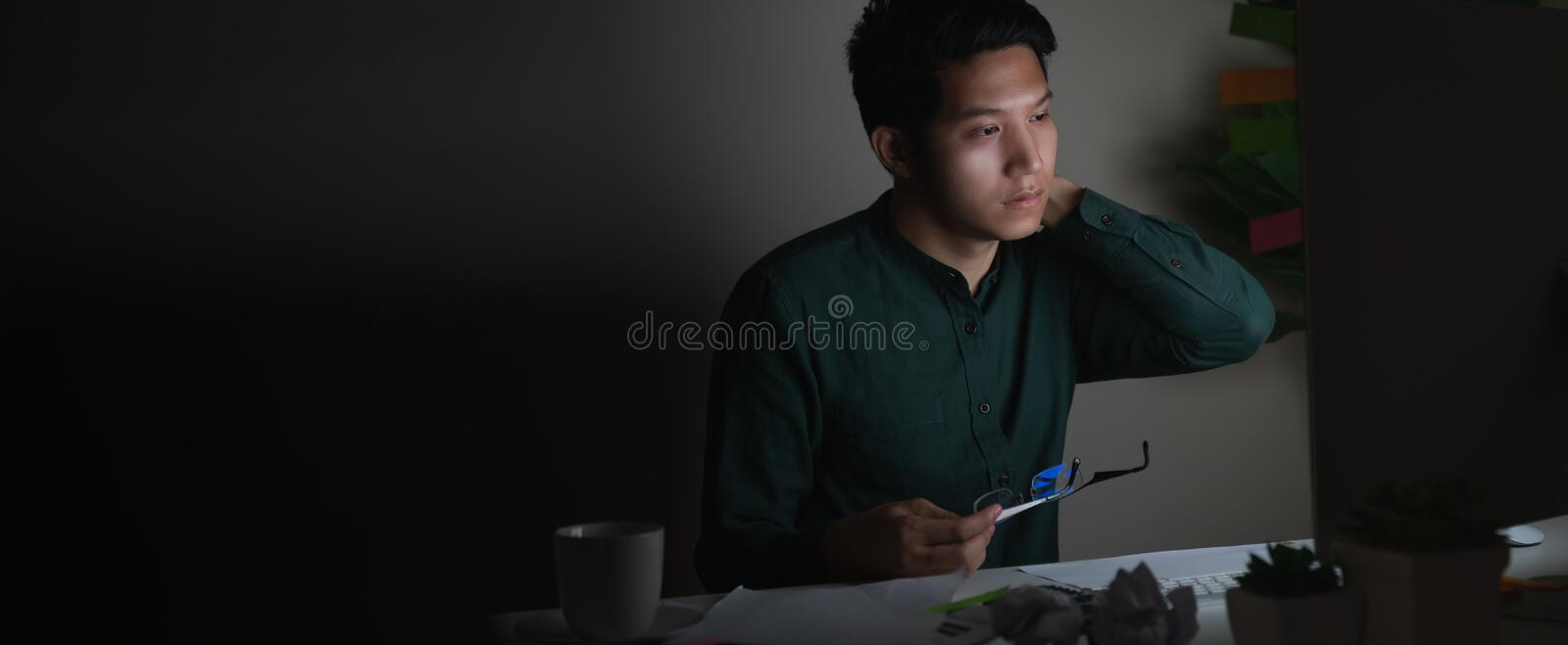 Attractive young asian man working late at night looking at laptop computer in dark home office desk feeling tired on work load or royalty free stock images