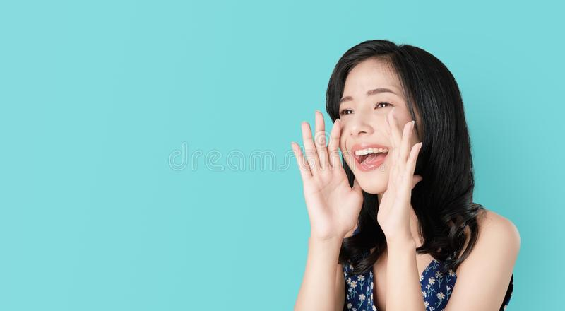 Attractive young asian woman announcing with hands to the mouth  and telling a secret, isolated on light blue background. stock photos