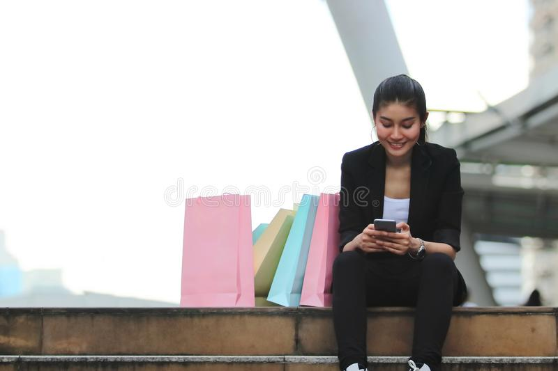 Attractive young Asian woman with colorful shopping bag sitting at outdoors stock images