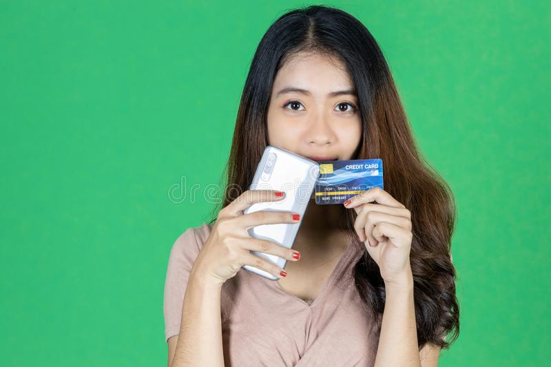 Attractive young Asian woman holding mobile smart phone and credit card on green isolated background. Shopping online concept.  stock images