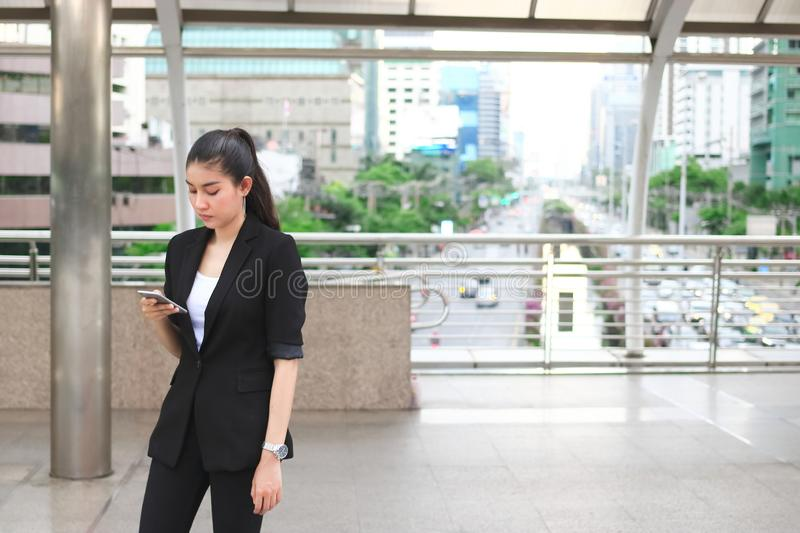 Attractive young Asian woman holding mobile smart phone on the street of city. Social network concept royalty free stock images