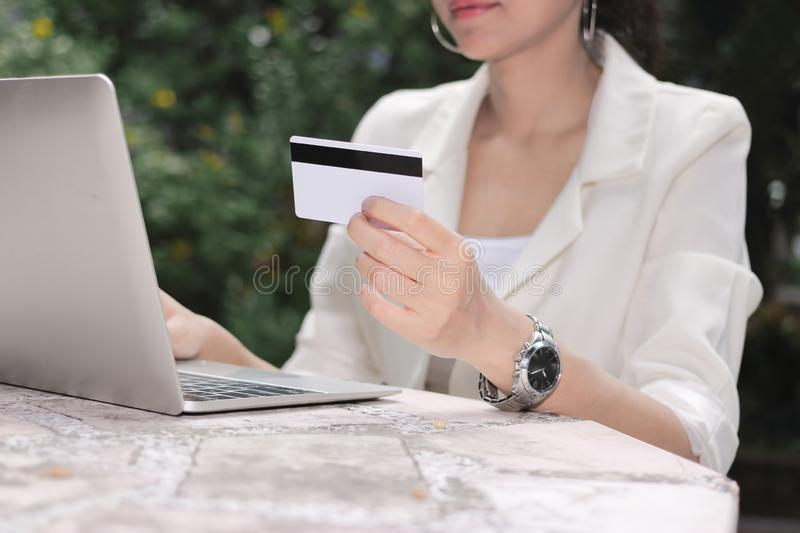 Attractive young Asian woman with laptop and credit card for shopping online stock photography