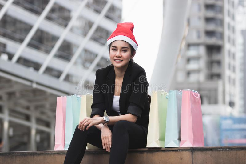 Attractive young Asian woman with santa hat and colorful shopping bag sitting outdoors after shopping for christmas gifts.  stock image