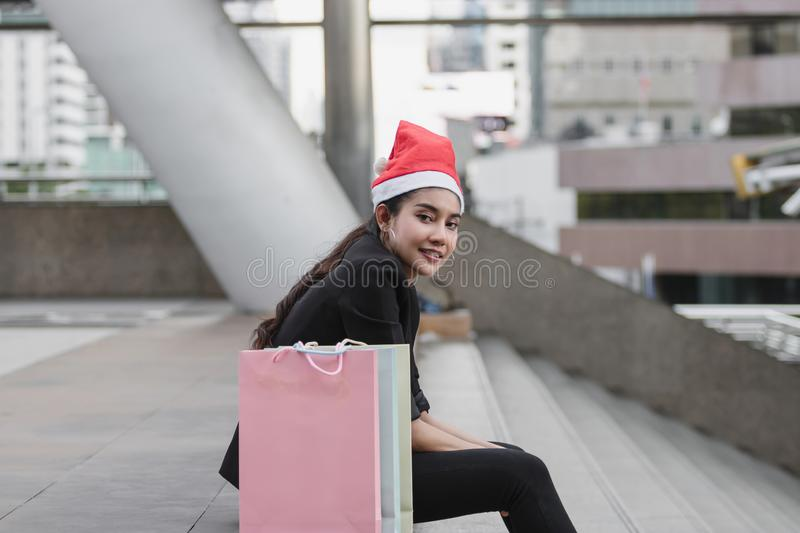 Attractive young Asian woman with santa hat and colorful shopping bag sitting outdoors after shopping for christmas gifts.  royalty free stock images