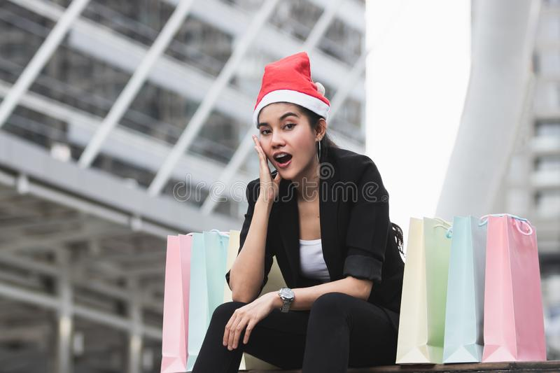 Attractive young Asian woman with santa hat and colorful shopping bag sitting outdoors after shopping for christmas gifts.  stock photography
