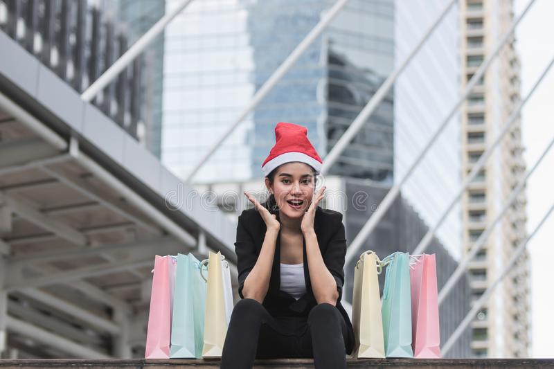Attractive young Asian woman with santa hat and colorful shopping bag sitting outdoors after shopping for christmas gifts.  royalty free stock photo