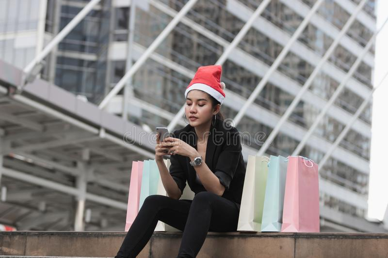 Attractive young Asian woman with santa hat and colorful shopping bag using mobile smart phone for shopping online for christmas g. Ifts stock photo