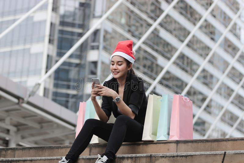 Attractive young Asian woman with santa hat and colorful shopping bag using mobile smart phone for shopping online for christmas g. Ifts stock photography