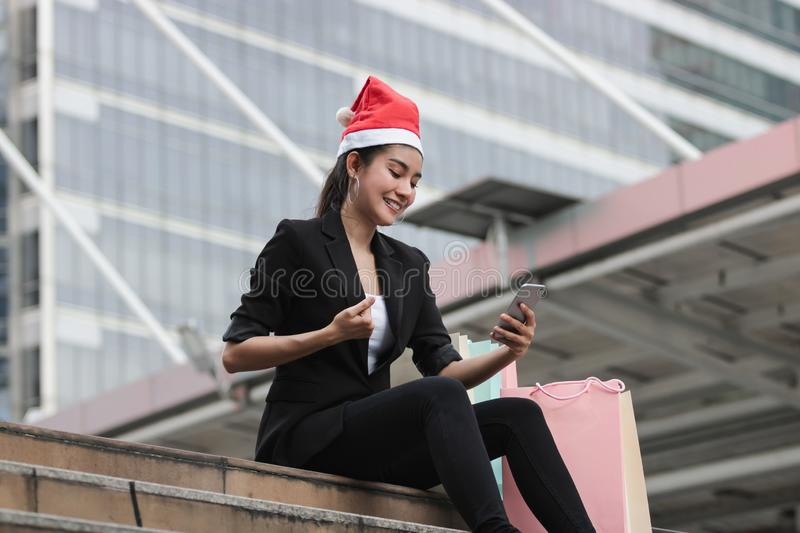 Attractive young Asian woman with santa hat and colorful shopping bag using mobile smart phone for shopping online for christmas g. Ifts royalty free stock photos
