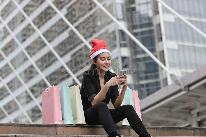 Attractive young Asian woman with santa hat and colorful shopping bag using mobile smart phone for shopping online for christmas g royalty free stock images