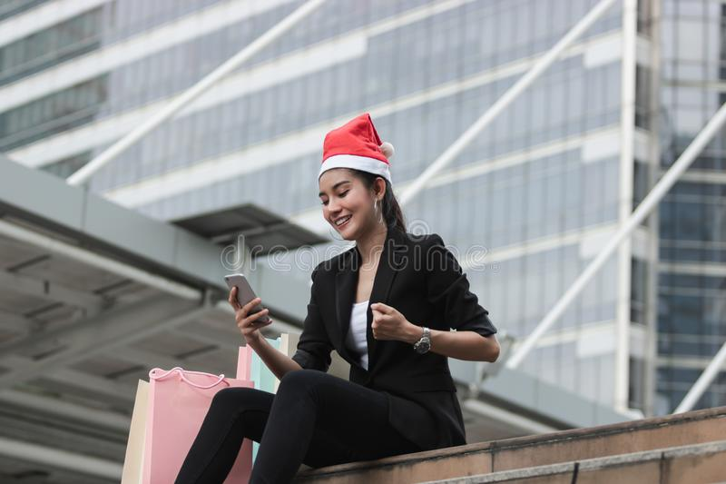 Attractive young Asian woman with santa hat and colorful shopping bag using mobile smart phone for shopping online for christmas g. Ifts royalty free stock images