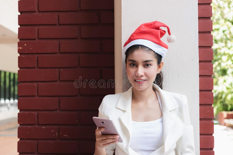 Attractive young Asian woman with santa hat using mobile smart phone for shopping online for christmas gifts.  stock photography
