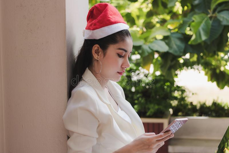 Attractive young Asian woman with santa hat using mobile smart phone for shopping online for christmas gifts.  stock images