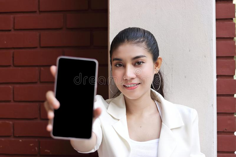 Attractive young Asian woman showing mobile smart phone in her hands. Internet of things concept.  stock photography