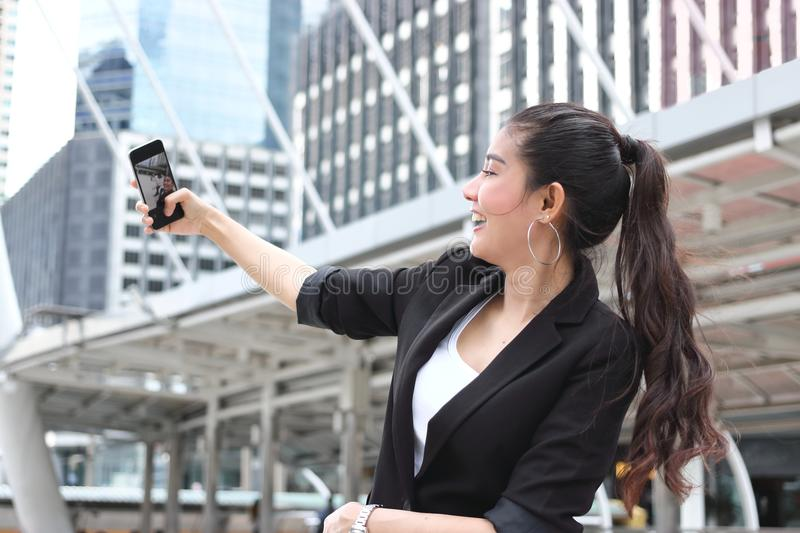 Attractive young Asian woman taking a photo or selfie with mobile smart phone on street of modern city. Attractive young Asian woman taking a photo or selfie stock photography