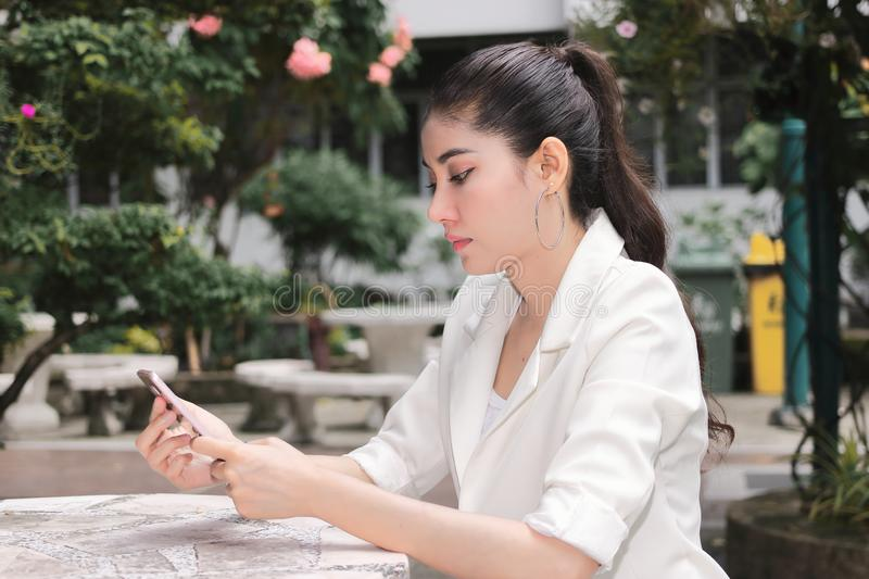 Attractive young Asian woman using mobile smart phone. Internet of things concept stock photos