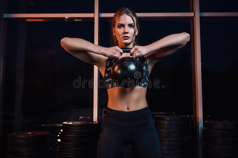 Attractive young athlete with muscular body exercising crossfit. Woman in sportswear doing crossfit workout with kettle royalty free stock images