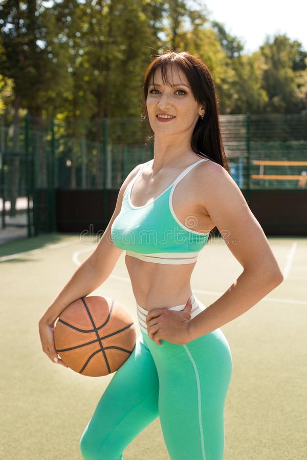 Attractive young athletic woman holding a basketball on a sports stadium, outdoors. Rest after training royalty free stock photo