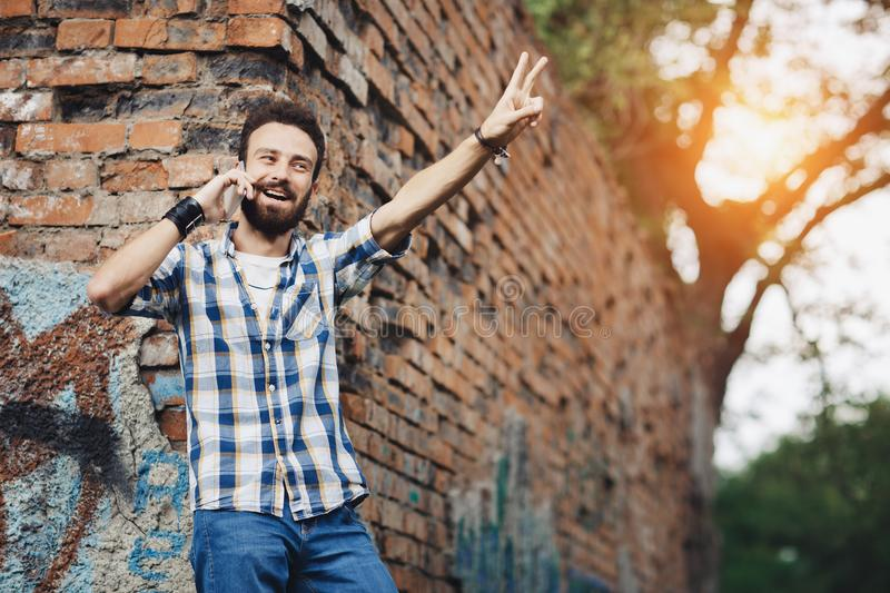 Attractive young bearded hipster with mobile phone. stock image