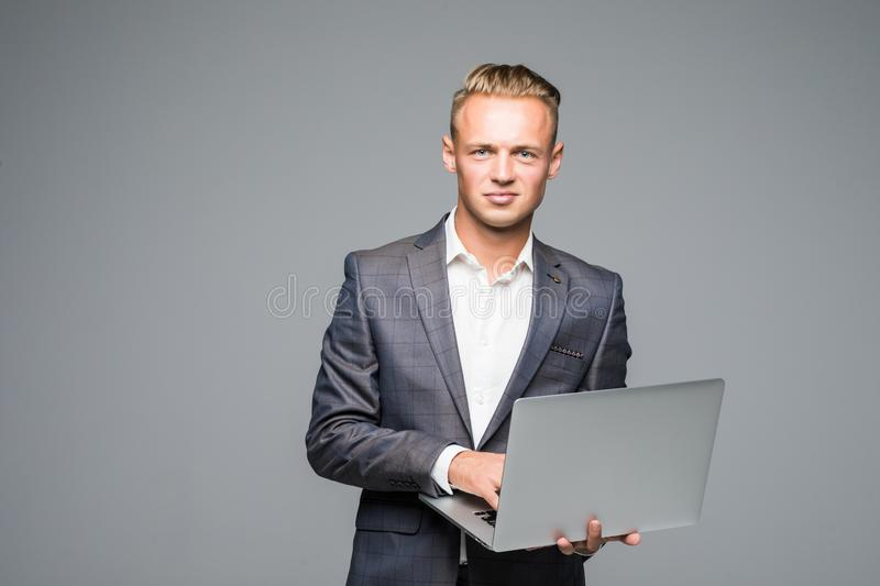 Attractive young blond businessman in classical suit using laptop standing against gray background royalty free stock photography