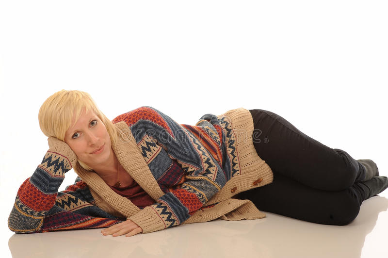 Attractive young blond woman. In colorful cardigan lying on white studio background stock image