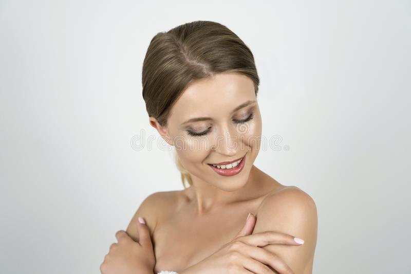 Attractive young blond woman half a turn holding hands near shoulders close up isolated white background stock photo