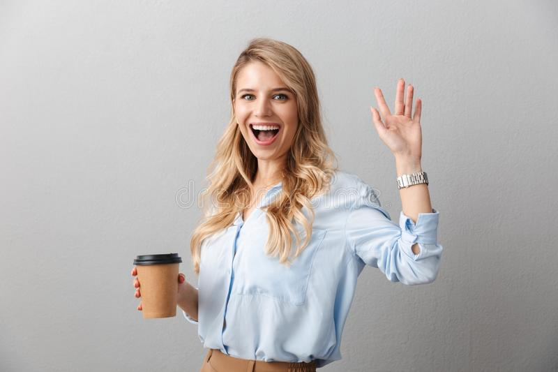 Attractive young blonde businesswoman wearing shirt. Standing isolated over gray background, holding takeaway coffee cup, waving hand stock photo