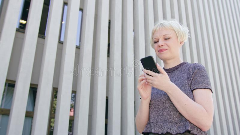 Young Blonde Lady Using a Phone in Town stock photography