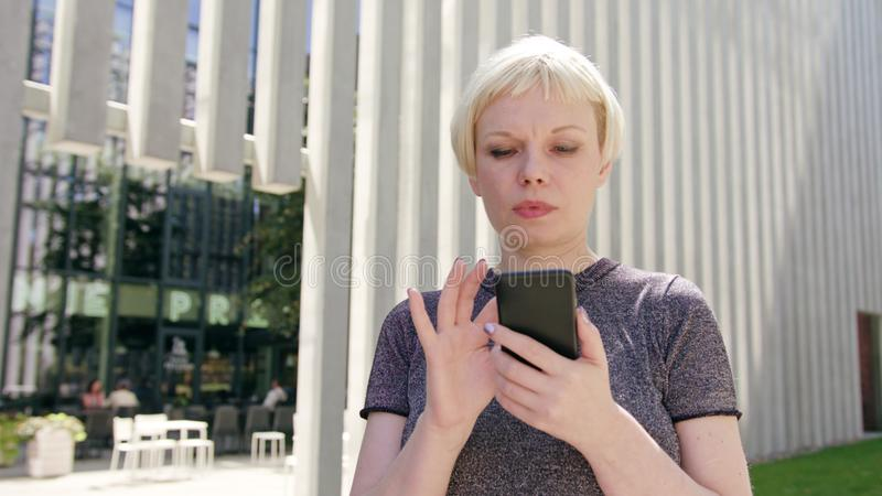 Young Blonde Lady Using a Phone in Town royalty free stock images
