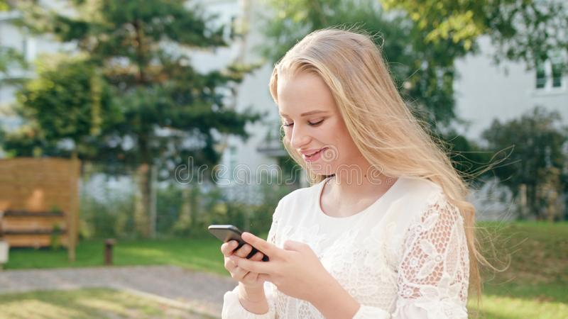 Young Blonde Lady Walking and Using a Phone in Town stock image