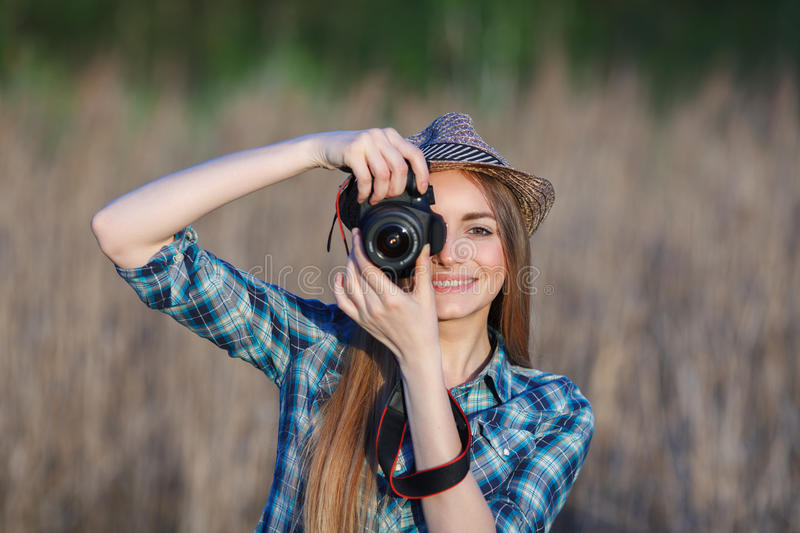 Attractive young blonde woman in blue plaid shirt straw hat enjoying her time taking photos on meadow outdoors. Attractive young blonde woman in blue plaid shirt stock photos