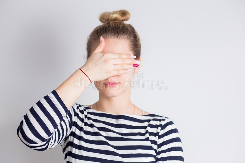 Attractive young blonde woman closing her eyes with hands. Portrait of beautiful girl, Surprise concept royalty free stock photography