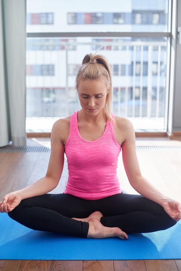 Attractive young blonde woman exercising and sitting in yoga lotus position. Yoga at home. Attractive young blonde woman exercising and sitting in yoga lotus stock image