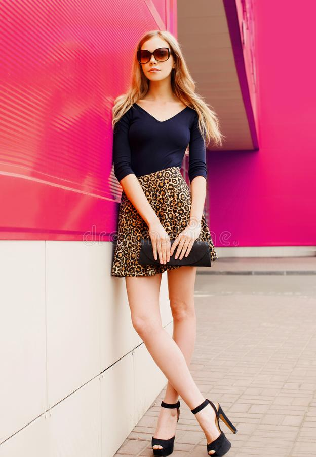 Attractive young blonde woman in leopard skirt, sunglasses with handbag clutch on city street stock photos