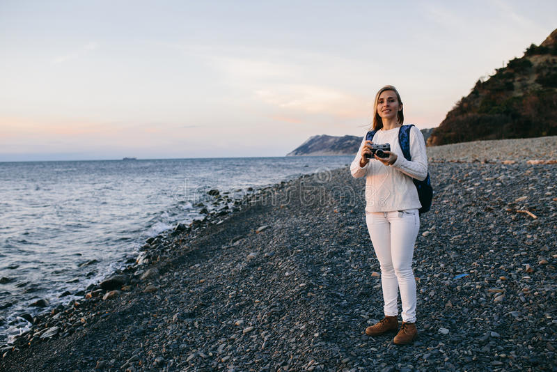Attractive young blonde woman tourist standing with an retro camera on beach royalty free stock photography