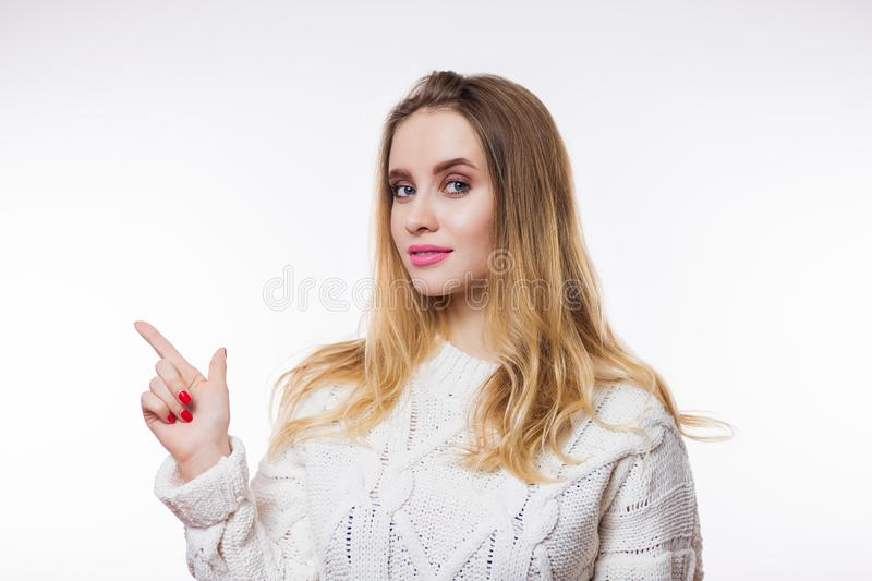Attractive young blonde woman wearing beige knitted sweater and finger pointing at copy space on white background stock photo