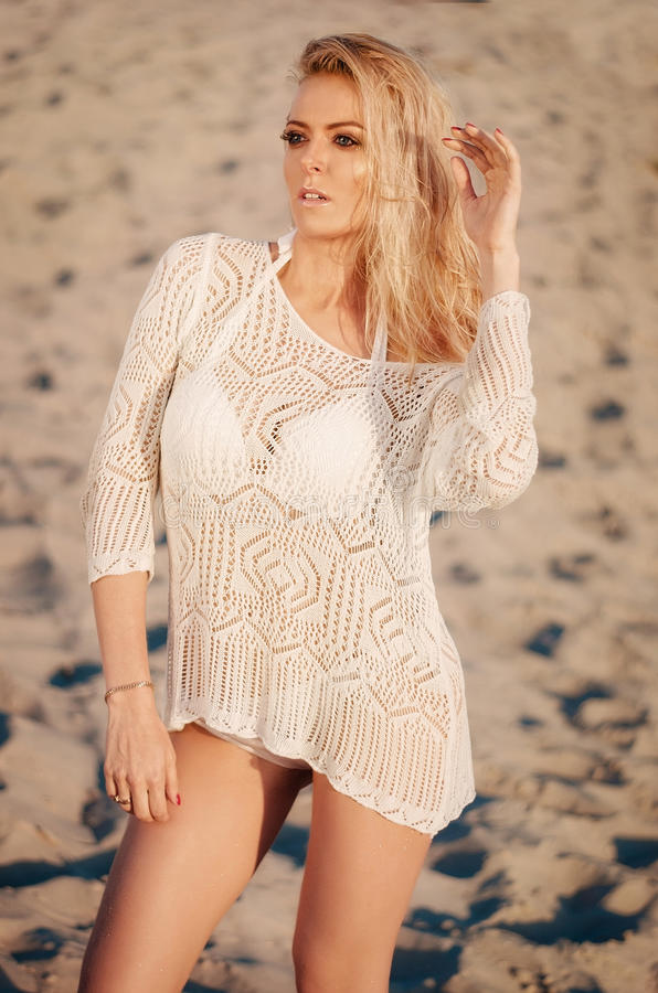 Attractive young blonde woman in white bikini on white sand. Beauty, fashion, vacation concept. stock images