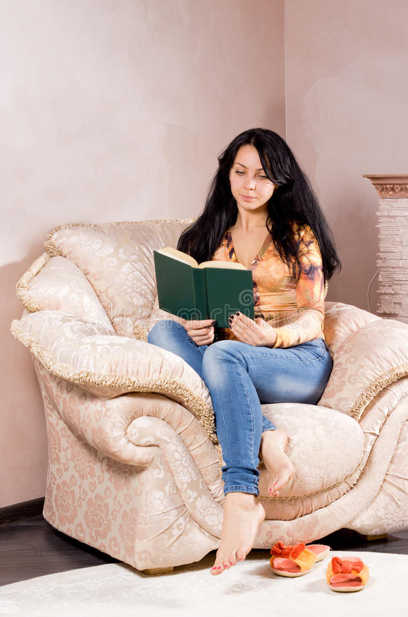 Woman curled up in an armchair reading. Attractive young brunette woman curled up in a comfortable cream upholstered armchair reading a book with her slip on stock images