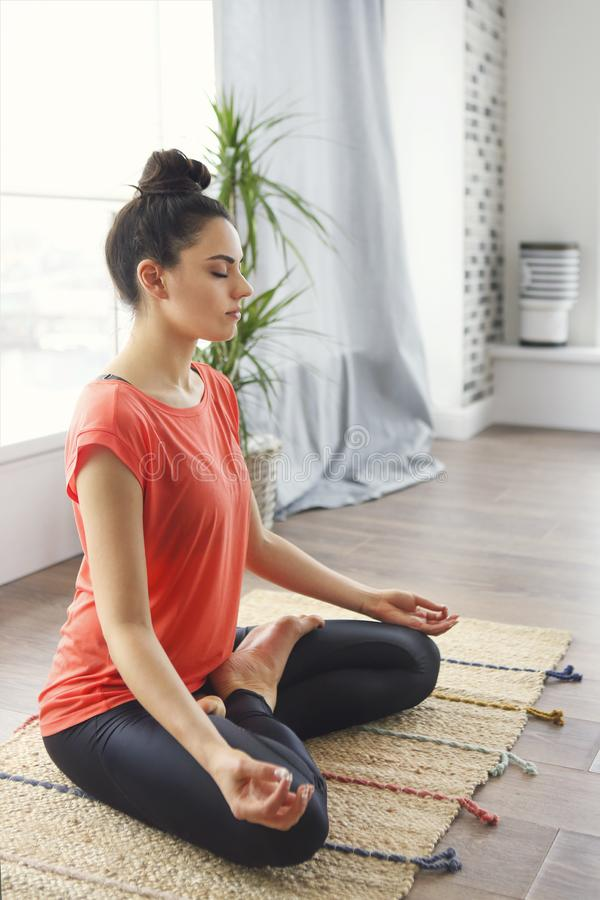 Attractive young woman exercising and sitting in yoga lotus position while resting at home stock photos