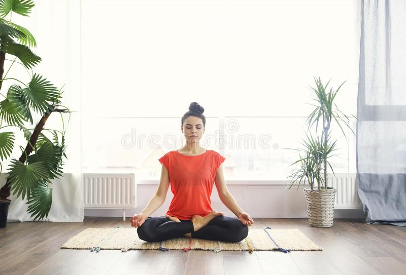 Attractive young woman exercising and sitting in yoga lotus position while resting at home stock images