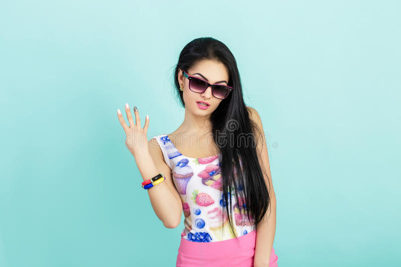 Attractive young brunette woman in pink tank top on blue background. girl in sunglasses shows four fingers stock image