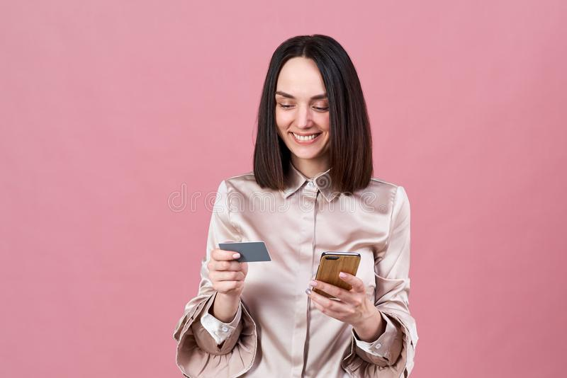 Attractive young brunette woman in a stylish blouse makes online purchases and uses a phone and a Bank card. royalty free stock photography