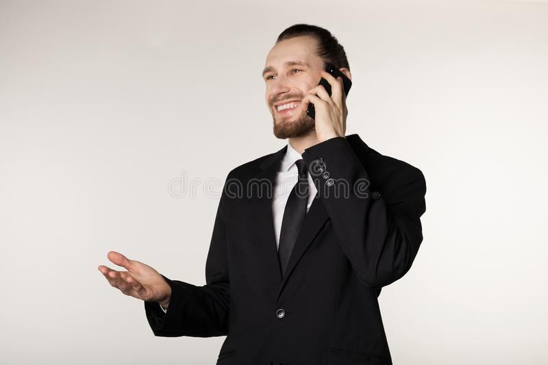 Attractive young busibessman in black suit smilig and talking on the phone with raised palm stock photography