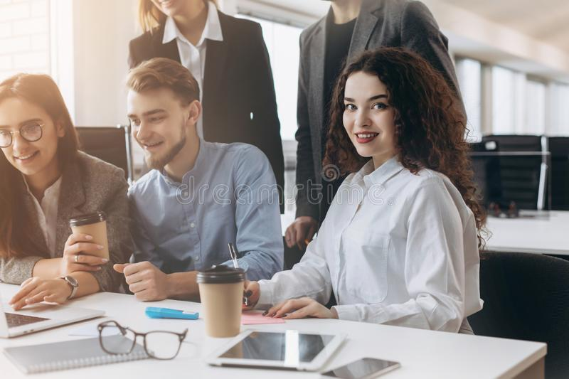 Attractive young business lady is looking at camera and smiling while her colleagues are working in the background royalty free stock images