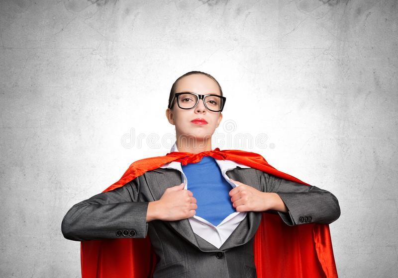 Attractive young business lady in red hero cape royalty free stock photography
