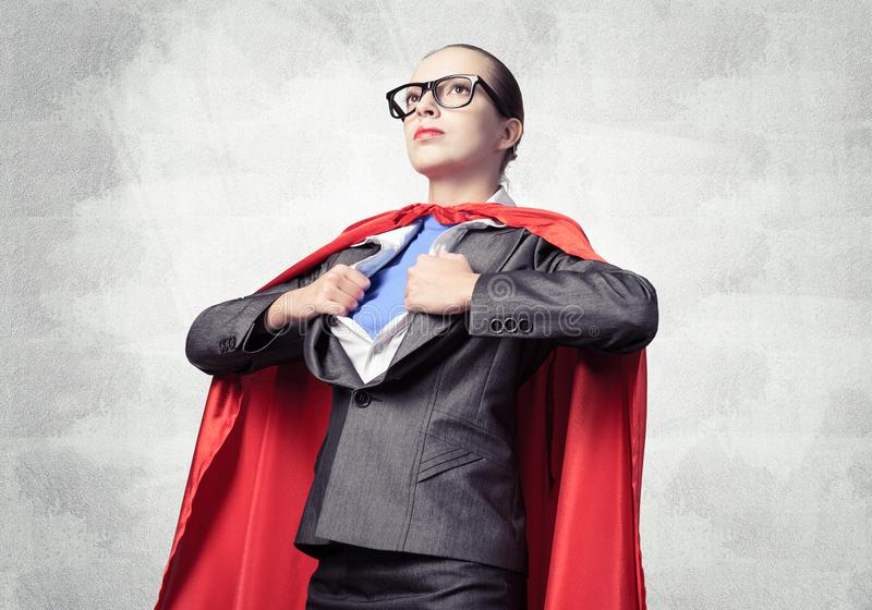 Attractive young business lady in red hero cape stock image